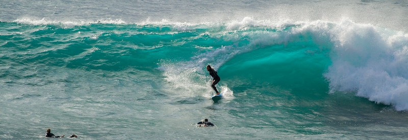 The surfer's carve thinned the wave and produced the lighter green streak.