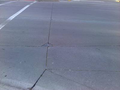 Pavement divot on SW corner of intersection of Douglas Ave & 6th Street