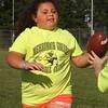 Isabella Molina, 7, of Billerica, hands off the ball at Merrimack Valley Pop Warner football skills clinic at Lampson Field. (SUN/Julia Malakie)