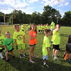 Kids wait in line to do a drill at Merrimack Valley Pop Warner football skills clinic at Lampson Field. (SUN/Julia Malakie)