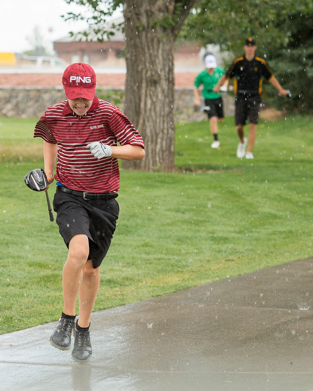 . Silver Creek golfer TJ Shehee runs through a brief rain shower Thursday afternoon August 11, 2016 during Northern Conference Golf action at the Olde Course in Loveland. More photos: BoCoPreps.com (Photo by Michael Brian/Loveland Reporter-Herald)