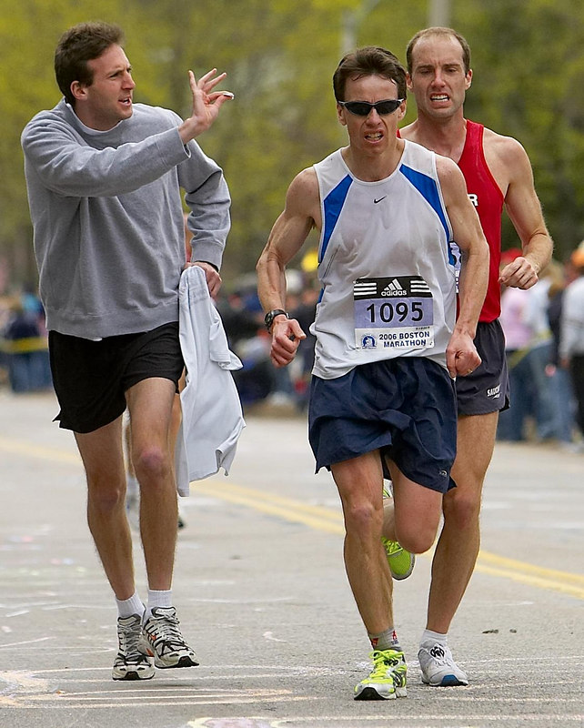 Greater Boston Track Club member Josh Sohn, left, offers teammate Kit Wells, far right, salt packets as he ascends Heartbreak Hill during the 2006 Boston Marathon in Newton, Mass., April 17, 2006.  Wells clocked 2:36:32 to finish 92nd overall.