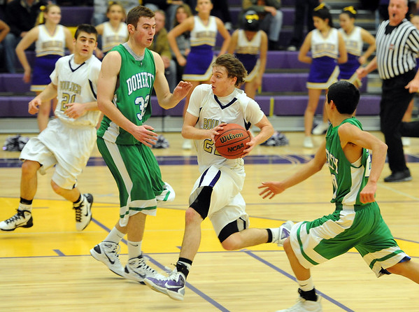 """Riley Grabau of Boulder High, on the fast break past Dylan Sisneros (32) and  Wil Romero, both  of Doherty.<br /> For more photos of the game, go to  <a href=""""http://www.dailycamera.com"""">http://www.dailycamera.com</a>.<br /> Cliff Grassmick/ February 26, 2011"""