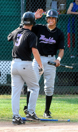 Boulder Eagles' Stephen Galambos, 3, is greeted by John Anagnost after Galambos scored in the first inning against Centaurus High School.<br /> Photo by Paul Aiken / The Camera / July 6, 2011