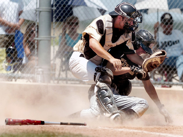 "Boulder's Loic Guegan, right, collides with Monarch catcher Greg Spurgin as he slides into home plate safely during a baseball game on Sunday, July 24, at Monarch High School in Louisville. Boulder defeated Monarch 13-9. For more photos of the game go to  <a href=""http://www.dailycamera.com"">http://www.dailycamera.com</a><br /> Jeremy Papasso/ Camera"