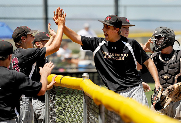 """Boulder's Ray Feigal, center, gets congratulated by his teammates after making the third out during a baseball game against the Monarch Coyotes on Sunday, July 24, at Monarch High School in Louisville. Boulder defeated Monarch 13-9. For more photos of the game go to  <a href=""""http://www.dailycamera.com"""">http://www.dailycamera.com</a><br /> Jeremy Papasso/ Camera"""