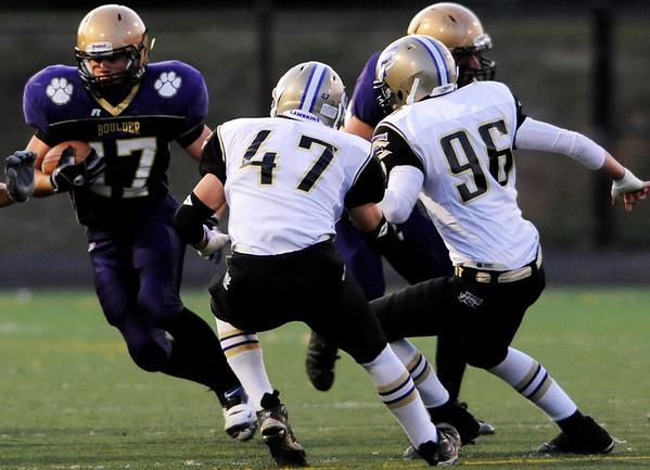 Boulder's Ethan Baker (17) carries the ball down the field as Fort Collins'  Lief Swanbom (47) and Bennett Ramirez (96) play defense during the game at Recht Field at Boulder High School in Boulder Thursday, Sept. 17, 2009.<br /> <br />  DAILY CAMERA/ Kasia Broussalian