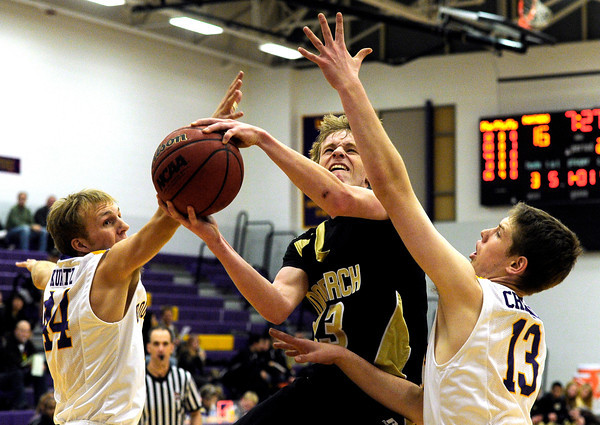 "Monarch High School's Kyle Billingsley drives to the hoop past Boulder High School's Andrew Kurtz, left, and Jonah Charnick during a basketball game on Friday, Jan. 13, at Boulder High School. Monarch won the game 50-49. For more photos of the game go to  <a href=""http://www.dailycamera.com"">http://www.dailycamera.com</a><br /> Jeremy Papasso/ Camera"