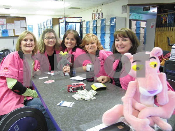 The girls of the team for Beisser Lumber pose between turns. They are Kathy Peterson, Jody Kayser, Dee Cummins, Julie Roest, Carla Filloon, and team mascot the Owens Corning Pink Panther.