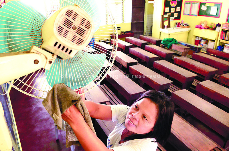 CEBU. As if preparing her lessons and other teaching-related tasks wasn't demanding enough, school teacher Benigna Dungog finds the time to clean up her Grade 1 room in the Zapatera Elementary School. (Amper Campaña)
