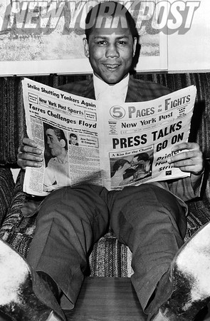 Lightweight Champion, Jose Torres, reads about his victory in the New York Post. 1964