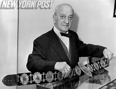 Nat Fleischer holds up gold belt containing mementos of each featherweight bout from 1937 to 1950. 1965
