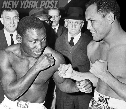 Dick Tiger and Jose Torress square off at weigh in before boxing match. 1967