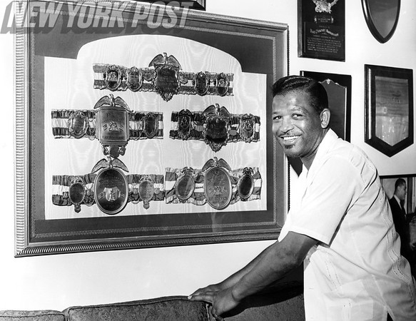 Ray Sugar Ray Robinson shows off his title belts.