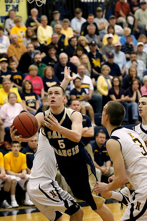 Record-Eagle/Jan-Michael Stump<br /> Traverse City St. Francis's Nicholas Clear (5) splits Negaunee's Tanner Uren (23) and Brock Weaver (3) in Tuesday's state quarterfinal game in Petoskey.