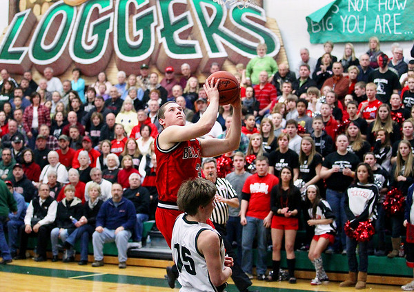 Record-Eagle/Keith King<br /> Bellaire's Reece Koepke takes the ball toward the basket against Boyne Falls' Forrest Williams Friday, March 9, 2012 at Boyne Falls Public School.
