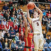 BRANDEN BEACHY | THE GOSHEN NEWS<br /> <br /> Goshen senior CJ Detweiler puts a shot up under the basket in front of Elkhart Memorial junior Jose Soto during 4A sectional semifinal play Friday.