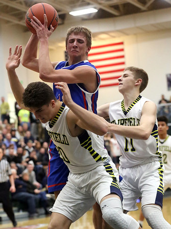 JAY YOUNG | THE GOSHEN NEWS<br /> West Noble sophomore Trevor Franklin secures a rebound away from Fairfield's Skylar Mast (20) and Luke Stephens (11) during their 3A sectional championship game on Saturday night.