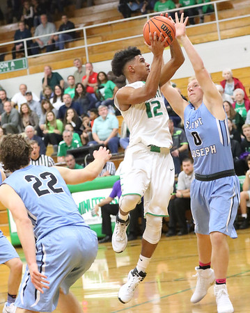JAY YOUNG | THE GOSHEN NEWS<br /> Concord senior Cedric Mitchell (12) takes the ball to the hoop as he slices between Saint Joseph defenders Joel Stangebye (0) and Michael Manion (22) during their game Tuesday evening in Dunlap.