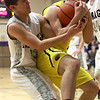 JAY YOUNG | THE GOSHEN NEWS<br /> Fairfield junior Caleb Goeglein, right, wraps up a rebound with both hands as Elkhart Christian Academy sophomore Ryan Charles tries to pull the ball away during their game Tuesday night in Elkhart.