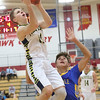 JAY YOUNG   THE GOSHEN NEWS<br /> Fairfield junior Luke Stephens hangs in the air as he sails past East Noble freshman Hayden Jones during their game in the 2016 Holiday Basketball Tournament hosted by Goshen High.
