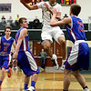 JAY YOUNG | THE GOSHEN NEWS<br /> Fairfield sophomore Cordell Hofer, center, hangs in the air as he looks for a teammate to dish the ball off to while being pressured by West Noble defenders Trevor Franklin (23) and Mason Stover (13) during their 3A sectional championship game on Saturday night.