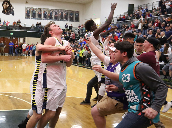 JAY YOUNG | THE GOSHEN NEWS<br /> Fairfield junior Shandon is hugged from behind by a teammate while students rush the court following their 3A sectional championship victory over West Noble on Saturday night in Syracuse.