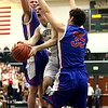 JAY YOUNG | THE GOSHEN NEWS<br /> Fairfield junior Luke Stephens, center, slips between a West Noble double team by Larry Nickolson (35) and Trevor Franklin, left, as he makes his way to the hoop during their 3A sectional championship game on Saturday night.