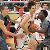 JAY YOUNG | THE GOSHEN NEWS<br /> Goshen's Will Line (11) draws a foul as he splits Marian defenders Kyron King, right, and Zach Lattimer, left, during their game on Tuesday evening at GHS.