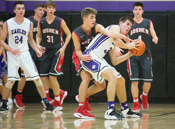 JAY YOUNG | THE GOSHEN NEWS<br /> Goshen High senior Eliot Nafziger reaches over the back of Elkhart Christian Academy senior Jonah Jara Wallick (30) as he tries to take the ball away during their game Tuesday night in Elkhart.