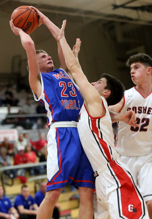 JAY YOUNG | THE GOSHEN NEWS West Noble sophomore Trevor Franklin (23) hangs in the air to get a shot off over Goshen High defenders Michael Pinarski and Porter Revoir (32) during their game Tuesday night at Goshen High School.