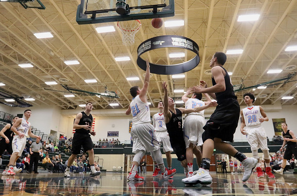 JAY YOUNG | THE GOSHEN NEWS<br /> NorthWood senior Luke Vincent Miranda (5) flips up a shot as he falls between Lakeland defenders Jeffrey Patrick (21) and Camron Bontrager (23) during the quarterfinals of the 3A sectional Tuesday night at Wawasee High School in Syracuse.