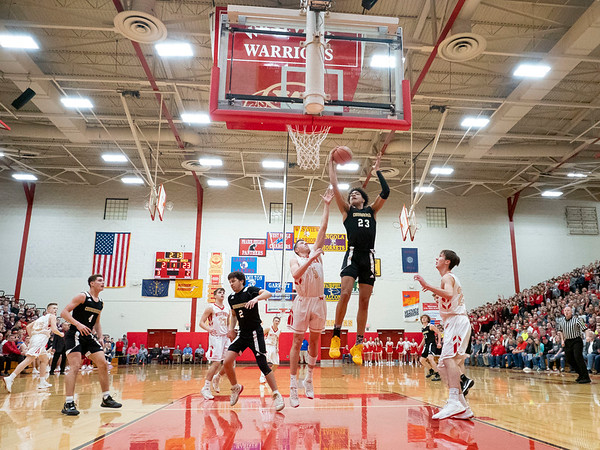 Churubusco Eagles forward Landen Jordan (23) snags a rebound against Westview Warriors forward Charlie Yoder (5) during the Friday night game at Westview High School in Topeka.
