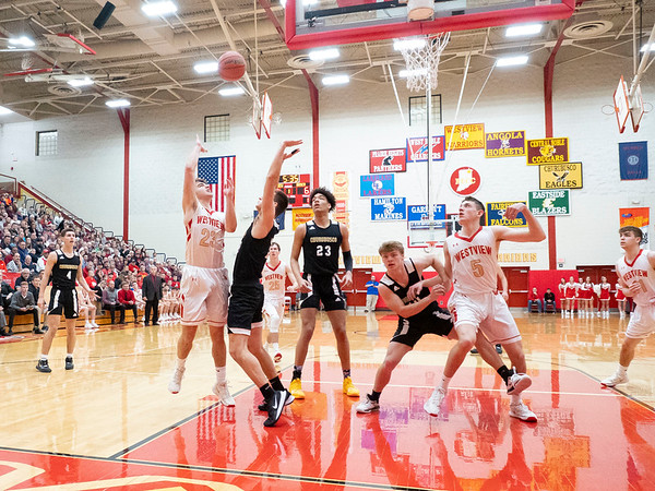 Westview Warriors forward Lyndon Miller (23) shoots a basket against Churubusco Eagles forward Hunter Perlich (3) during the Friday night game at Westview High School in Topeka.