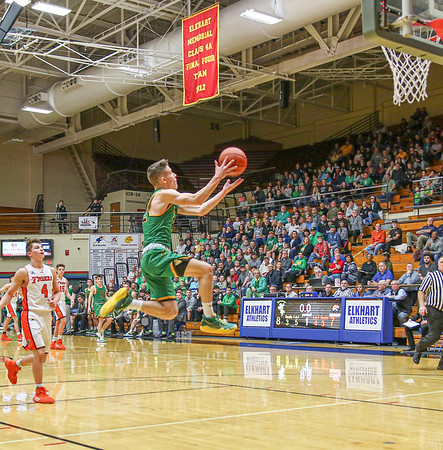 Northridge junior Carter Stoltzfus (12) catches a full court end of the<br /> period shot and attempts to lay it during the Elkhart Sectional<br /> championship game Saturday night.