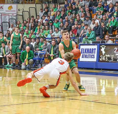 Northridge junior Clay Stoltzfus (14) takes advantage of a slip by<br /> Warsaw senior Keagan Larsh (3) to drain a 3-point shot as the Raiders go<br /> on to defeat the Tigers for the sectional championship.