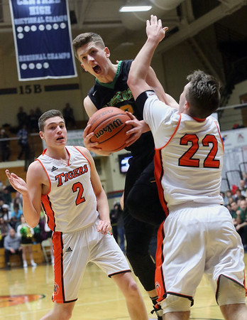 JAY YOUNG | THE GOSHEN NEWS<br /> Northridge senior Luke Morrison, center, splits Warsaw defenders Kyle Mangas (2) and Jaceb Burish (22) as he gets to the basket during their 4A sectional tournament game Wednesday night at Northside Gym in Elkhart.,
