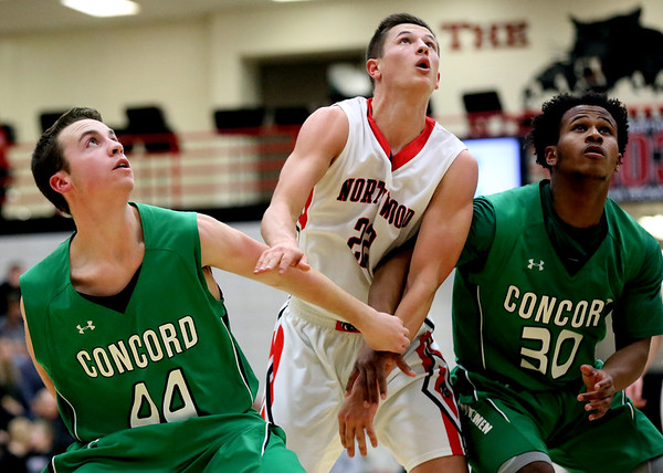 JAY YOUNG | THE GOSHEN NEWS<br /> Concord's Matt Auger (44) and Marvell Danner (30) work to block out NorthWood junior Caleb Lung (22) during their game Thursday night in Nappanee.