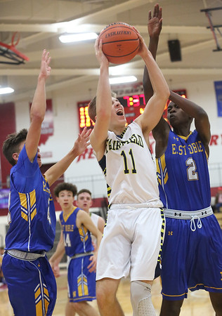 JAY YOUNG | THE GOSHEN NEWS<br /> Fairfield junior Luke Stephens (11) gets between East Noble defenders Ali Ali (2) and Hayden Jones, left, as he gets to the basket during their game in the 2016 Holiday Basketball Tournament hosted by Goshen High.