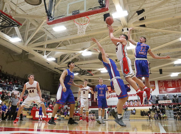 JAY YOUNG | THE GOSHEN NEWS<br /> Goshen High senior Mitchell Walters (24) gets off a shot while avoiding West Noble defenders Trevor Franklin (23) and Jace Dooley during their game on Tuesday night at Goshen High School.