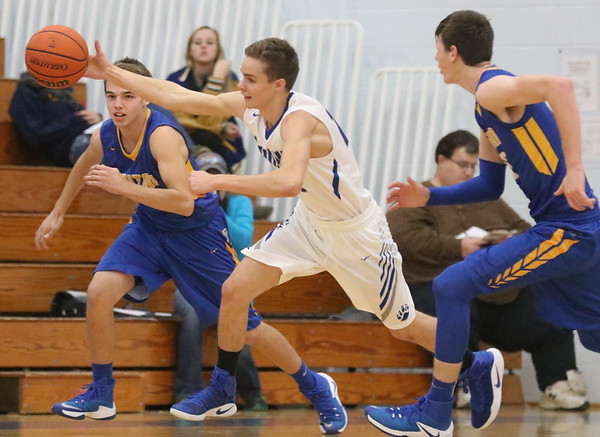 JAY YOUNG   THE GOSHEN NEWS<br /> Bethany Christian junior Seth Brenneman, center, takes off down court as he swoops in to steal the ball while Triton's Caden Marr, left, and Grant Johnson, right, give chase during their game Tuesday night at Bethany.