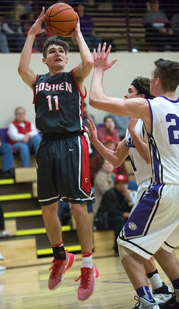 JAY YOUNG | THE GOSHEN NEWS<br /> Goshen High junior Will Line (11) pulls up for a jump shot in front of a pair of Elkhart Christian Academy defenders during their game Tuesday night in Elkhart.