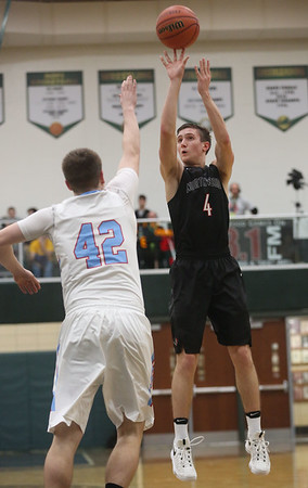 JAY YOUNG | THE GOSHEN NEWS<br /> NorthWood senior Luke Zurcher (4) fires a three point shot over Lakeland junior Drew Grossman (42) during the quarterfinals of the 3A sectional Tuesday night at Wawasee High School in Syracuse.