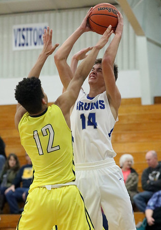 JAY YOUNG | THE GOSHEN NEWS<br /> Bethany junior Seth Brenneman (14) is challenged by Fairfield sophomore Cordell Hofer (12) as he takes a shot during their game Tuesday evening in Goshen.