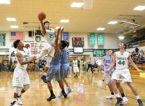 JAY YOUNG | THE GOSHEN NEWS<br /> Concord senior Denzel Halliburton (20) hangs in the air as he gets to the rim over Saint Joseph defenders Muhammad Shabazz (13) and Michael Manion (22) during their game Tuesday evening in Dunalp.