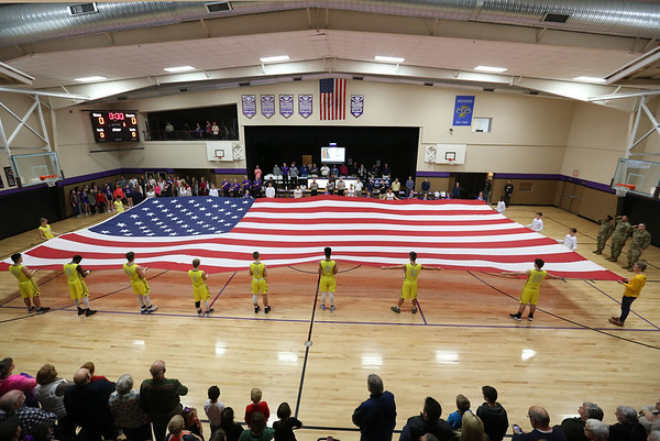 JAY YOUNG | THE GOSHEN NEWS<br /> Fairfield and Elkhart Christian Academy players hold a giant flag in honor of the armed forces before the start of their game Tuesday night in Elkhart.