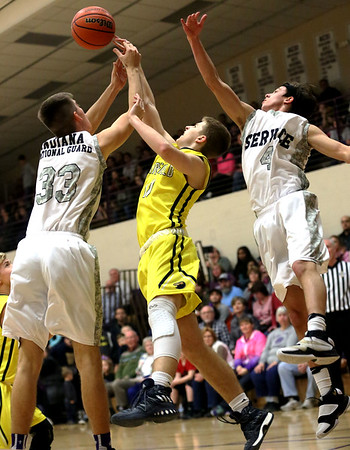 JAY YOUNG | THE GOSHEN NEWS<br /> Fairfield junior Luke Stephens, center, fights with Elkhart Christian Academy's Jonah Jara Wallick (33) and Jakob Maxwell (4) for a rebound during their game Tuesday night in Elkhart.