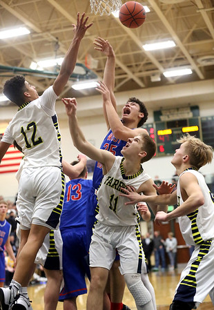 JAY YOUNG   THE GOSHEN NEWS<br /> West Noble senior Larry Nickolson (35) flips up a shot over the outstretched hand of Fairfield sophomore Cordell Hofer (12)  while Luke Stephens (11) gets into rebounding position during their 3A sectional championship game on Saturday night.
