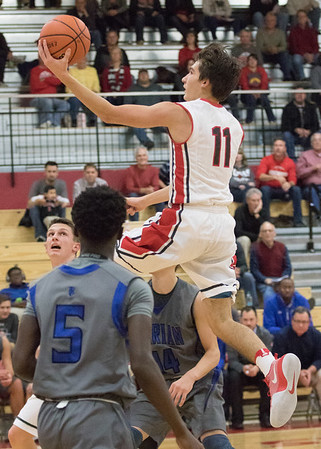 JAY YOUNG | THE GOSHEN NEWS<br /> Goshen's Will Line (11) floats between Marian defenders Kyron King (5) and Zach Lattimer (14) as he goes in for an easy two points during their game on Tuesday evening at GHS.