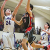 JAY YOUNG | THE GOSHEN NEWS<br /> Goshen High junior Will Line (11) drives to the basket against Elkhart Christian Academy defenders Weston Sage (24) and Jakob Maxwell during their game Tuesday night in Elkhart.